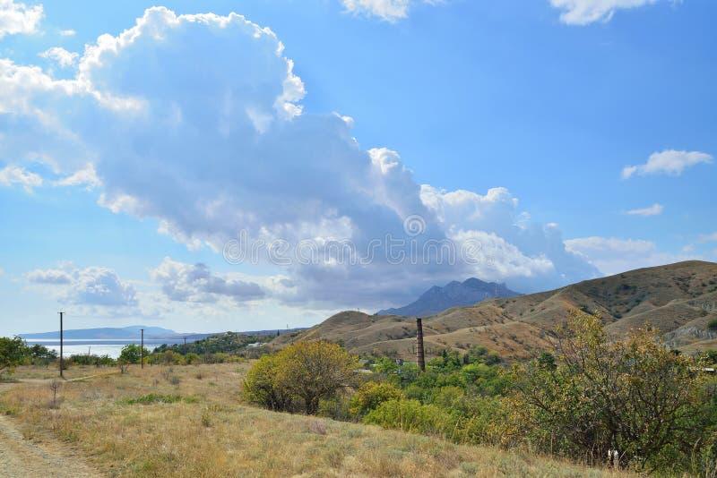 Το σύννεφο εμφανίζεται από πίσω από τα βουνά στο Karadag Nati στοκ εικόνες