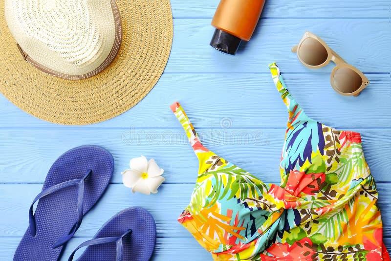 Το σύνολο ζωηρόχρωμων εξαρτημάτων γυναικών ` s στο μαγιό εποχής παραλιών, τα γυαλιά ηλίου, οι πτώσεις κτυπήματος, sunscreen και τ στοκ φωτογραφίες με δικαίωμα ελεύθερης χρήσης
