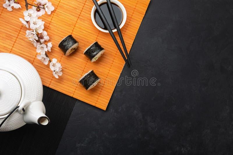Το σύνολο σουσιών και maki κυλά με τον κλάδο των άσπρα λουλουδιών και teapot στον πίνακα πετρών στοκ φωτογραφία με δικαίωμα ελεύθερης χρήσης