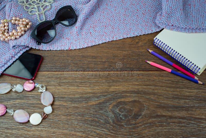 Το σύνολο των γυναικών εξαρτημάτων κινητού κοσμήματος γυαλιών χρωματισμένου σημειωματάριο μολυβιών ξύλινου σκοτεινού επιπέδου άπο στοκ εικόνα με δικαίωμα ελεύθερης χρήσης