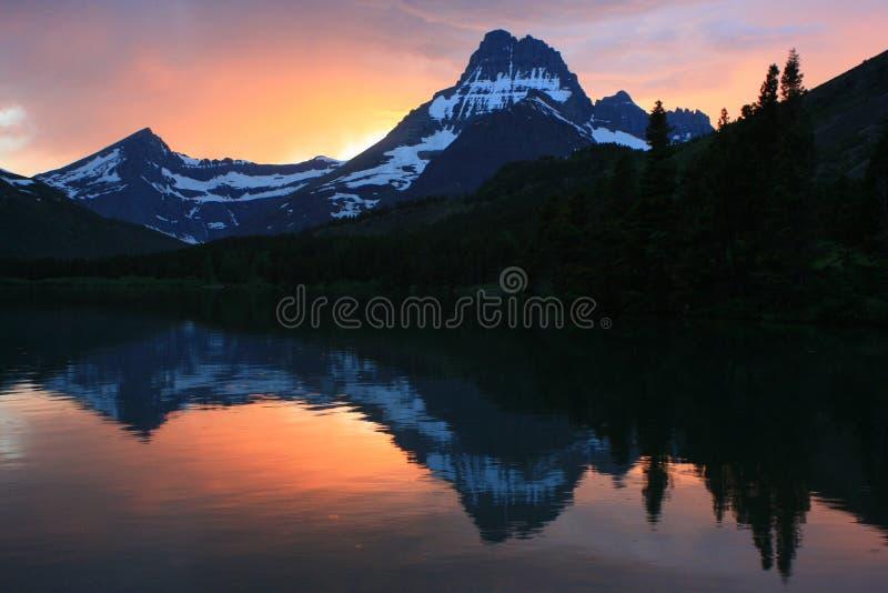 Γρήγορη τρέχουσα λίμνη στο εθνικό πάρκο παγετώνων ηλιοβασιλέματος στοκ εικόνα
