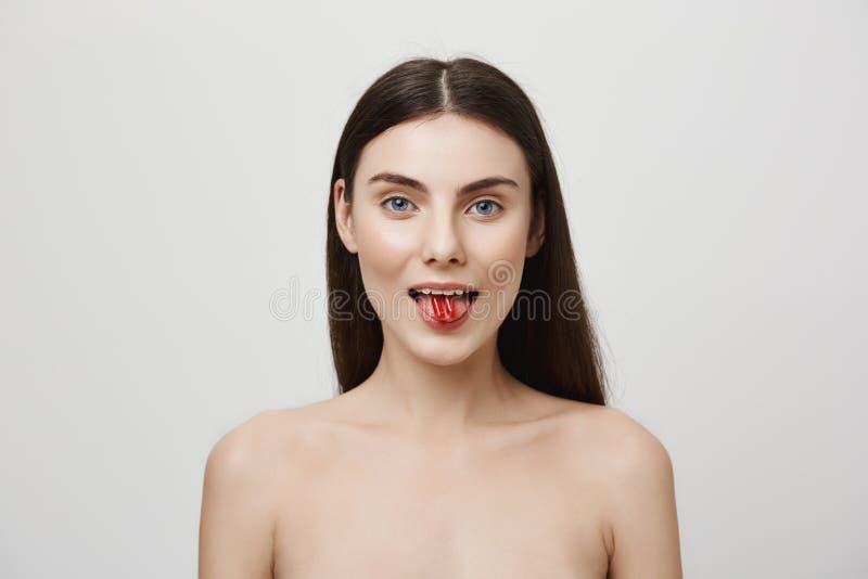 Το σώμα χρειάζεται τις βιταμίνες κάθε μέρα Πορτρέτο της όμορφης νέας καυκάσιας γυναίκας που κολλά έξω τη γλώσσα και που κρατά δύο στοκ εικόνες
