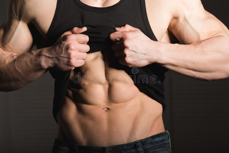 Το τέλειο άτομο παρουσιάζει ABS έξι πακέτων του Μυϊκός και κατάλληλος κορμός του νέου αρσενικού Hunk με το αθλητικό πουκάμισο εκμ στοκ φωτογραφία με δικαίωμα ελεύθερης χρήσης