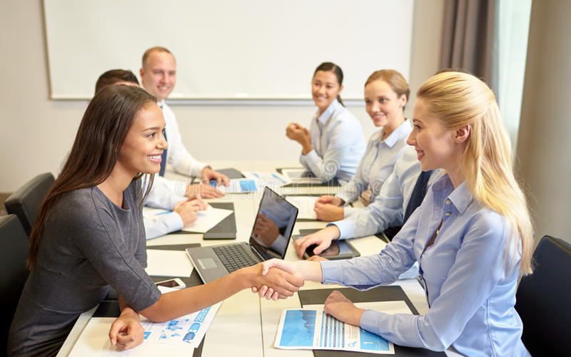 Το τίναγμα επιχειρηματιών χαμόγελου παραδίδει το γραφείο στοκ φωτογραφία
