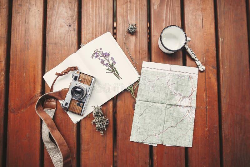το ταξίδι και wanderlust επίπεδος βάζει Η τοπ άποψη της κάμερας φωτογραφιών, χάρτης, σημειωματάριο, κούπα, σύλλεξε τα wildflowers στοκ εικόνα