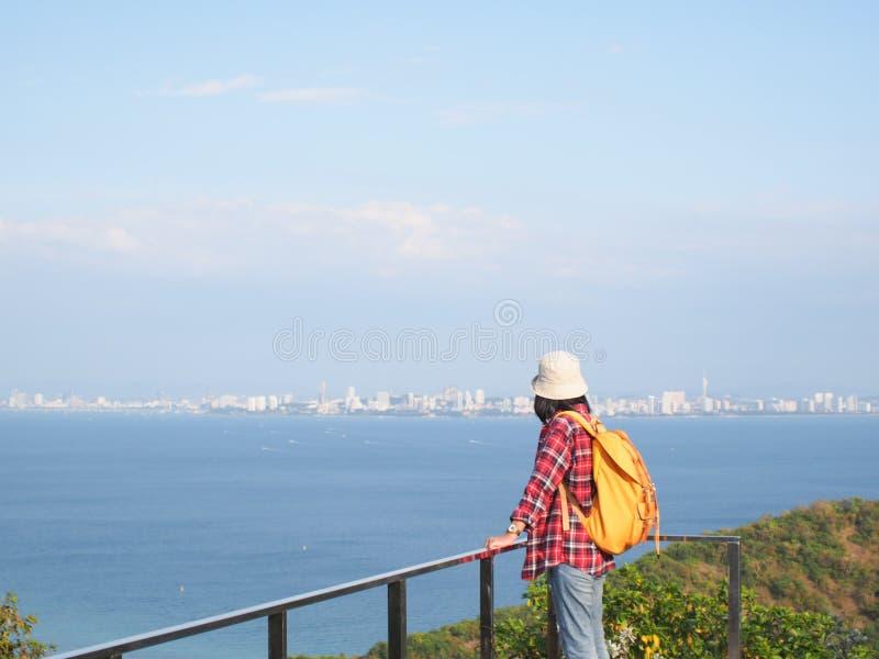 Το ταξίδι, οι γυναίκες που φορούν το τζιν παντελόνι και το κόκκινο πουκάμισο καρό και κίτρινα στην άποψη στο βουνό εξετάζουν τη θ στοκ εικόνες με δικαίωμα ελεύθερης χρήσης
