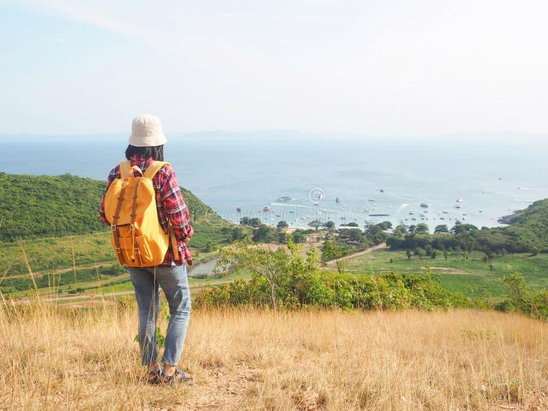 Το ταξίδι, οι γυναίκες που φορούν το τζιν παντελόνι και το κόκκινο πουκάμισο καρό και κίτρινα στην άποψη στο βουνό εξετάζουν τη θ στοκ φωτογραφία