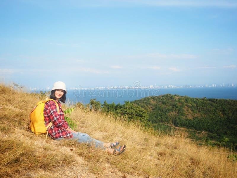 Το ταξίδι, οι γυναίκες που φορούν το τζιν παντελόνι και το κόκκινο πουκάμισο καρό και κίτρινα στην άποψη στο βουνό εξετάζουν τη θ στοκ φωτογραφίες