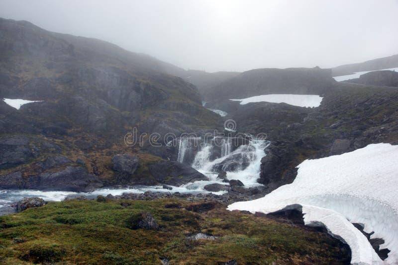 Το ταξίδι στη Νορβηγία, ο ποταμός ρέει από το βουνό, όπου υπάρχει ακόμα χιόνι τον Ιούνιο στοκ εικόνες
