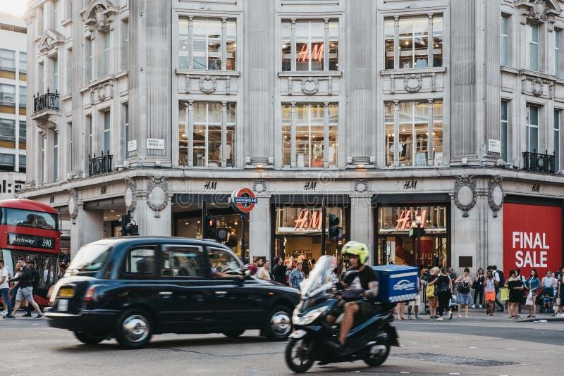 Το ταξί και οι άνθρωποι μπροστά από τη ναυαρχίδα H&M αποθηκεύουν στην οδό της Οξφόρδης, Λονδίνο, UK στοκ εικόνες