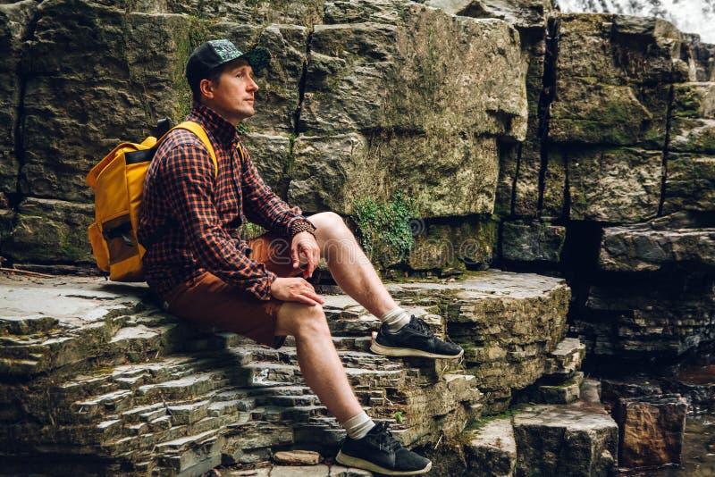 Το ταξιδιωτικό άτομο με ένα σακίδιο πλάτης κάθεται σε έναν απότομο βράχο ενάντια σε έναν καταρράκτη Διάστημα για το μήνυμα κειμέν στοκ φωτογραφία