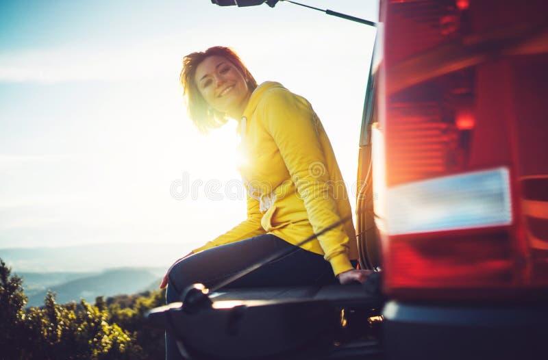Το ταξιδιωτικό ταξίδι τουριστών στο αυτοκίνητο στην πράσινη κορυφή στο βουνό, νέο κορίτσι χαμογελά ευτυχώς ενάντια στο ηλιοβασίλε