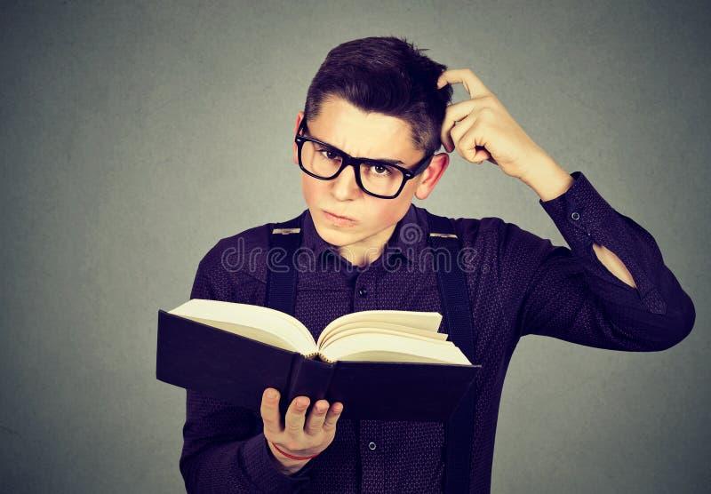 Το ταραγμένο άτομο στα γυαλιά περιέπλεξε μετά από να διαβάσει ένα βιβλίο στοκ εικόνα