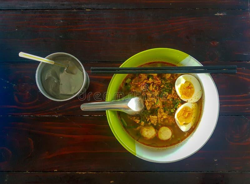 Το ταϊλανδικό τεμαχισμένο ύφος νουντλς χοιρινού κρέατος που διακοσμήθηκε με τις σφαίρες χοιρινού κρέατος, μισό-το βρασμένο αυγό στοκ φωτογραφίες