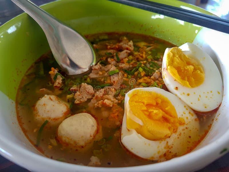 Το ταϊλανδικό ύφος τεμάχισε το νουντλς χοιρινού κρέατος που διακοσμήθηκε με τις σφαίρες χοιρινού κρέατος και μισό-το βρασμένο αυγ στοκ φωτογραφία με δικαίωμα ελεύθερης χρήσης
