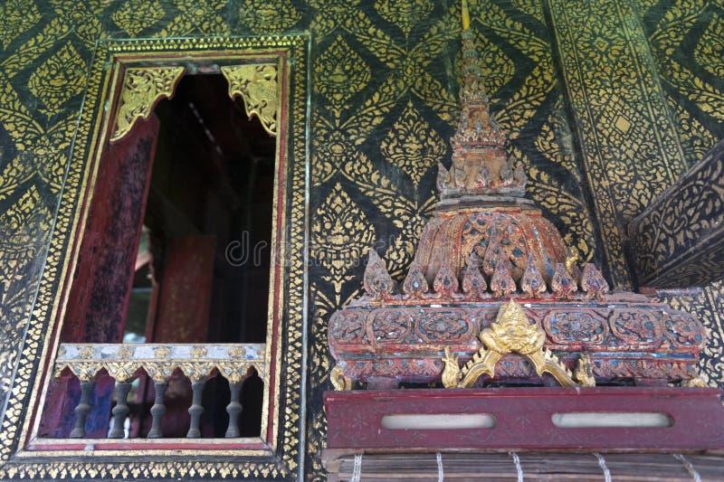 Το ταϊλανδικός-ύφος διακόσμησε το παράθυρο και επιχρύσωσε τον τοίχο, με το κιβώτιο scripture στο χαρασμένο ξύλινο ράφι στο ναό Wa στοκ φωτογραφία με δικαίωμα ελεύθερης χρήσης