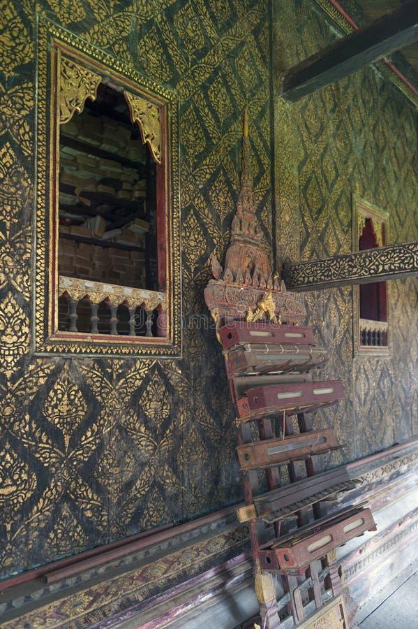 Το ταϊλανδικός-ύφος διακόσμησε το παράθυρο και επιχρύσωσε τον τοίχο, με το κιβώτιο scripture στο χαρασμένο ξύλινο ράφι στο ναό Wa στοκ φωτογραφίες