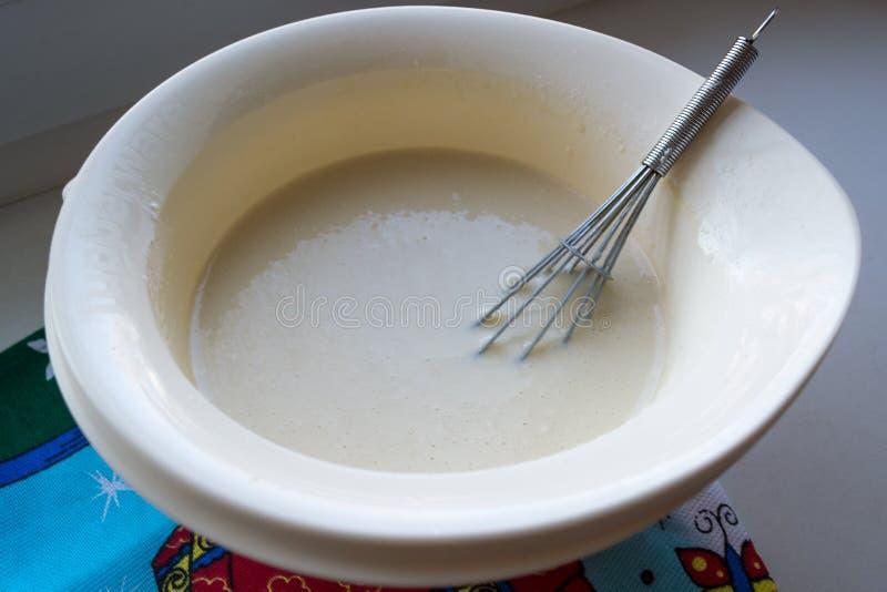 Το τελειωμένο κτύπημα τηγανιτών σε ένα άσπρο κύπελλο με ένα μέταλλο χτυπά ελαφρά στοκ εικόνες