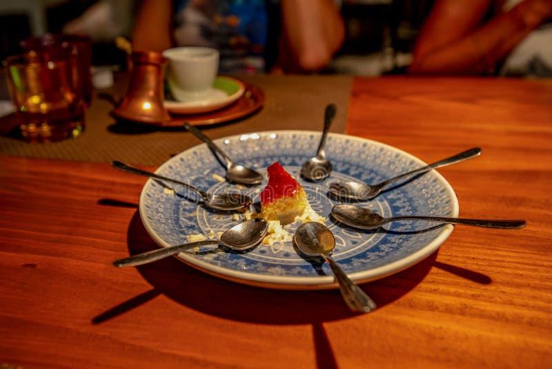 Το τελευταίο κομμάτι cheesecake και έξι κουταλιών στοκ φωτογραφία