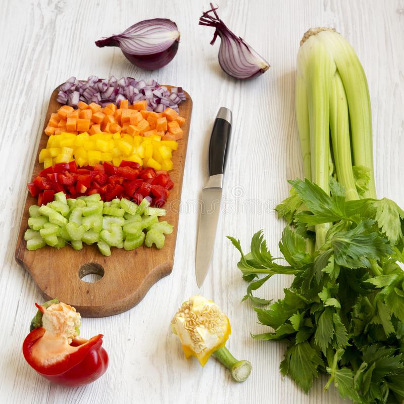 Το τεμαχισμένο καρότο φρέσκων λαχανικών, σέλινο, κρεμμύδι, χρωμάτισε τα πιπέρια που τακτοποιήθηκαν σε έναν τέμνοντα πίνακα σε μια στοκ φωτογραφίες με δικαίωμα ελεύθερης χρήσης