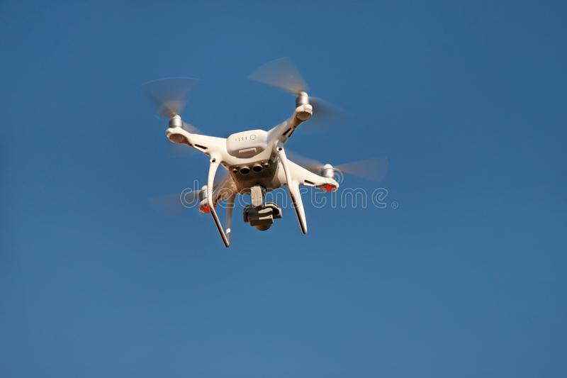 Το τετράγωνο κηφήνων copter πετά στο μπλε ουρανό στο υπόβαθρο Ο σύγχρονος κηφήνας πετά στον αέρα, για να πάρει τις φωτογραφίες κα στοκ φωτογραφία