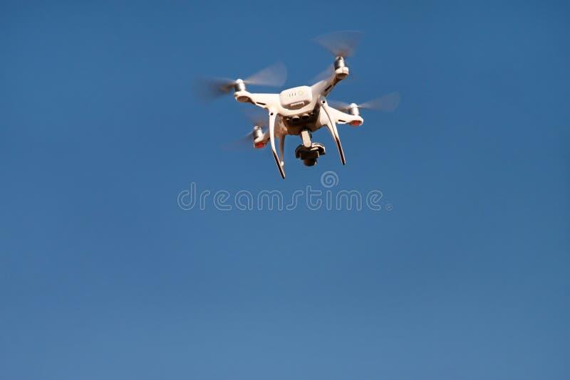 Το τετράγωνο κηφήνων copter πετά στο μπλε ουρανό στο υπόβαθρο Ο σύγχρονος κηφήνας πετά στον αέρα, για να πάρει τις φωτογραφίες κα στοκ εικόνα με δικαίωμα ελεύθερης χρήσης