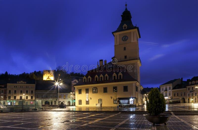Το τετράγωνο του Συμβουλίου κατά τη διάρκεια της βροχής σε Brasov, Ρουμανία Άποψη με τα διάσημα κτήρια το βράδυ στοκ φωτογραφία