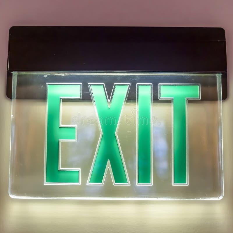 Το τετραγωνικό εσωτερικό κτηρίου πλαισίων με ένα σημάδι εξόδων πράσινου φωτός νέου στον άσπρο τοίχο στοκ εικόνες