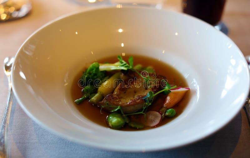 Το τηγάνι τα gras παπιών foie με τα πράσινα μπιζέλια και το γεύμα ασφαλίστρου μαρουλιού, μοναδική κουζίνα γεύματος πολυτέλειας στ στοκ εικόνες με δικαίωμα ελεύθερης χρήσης
