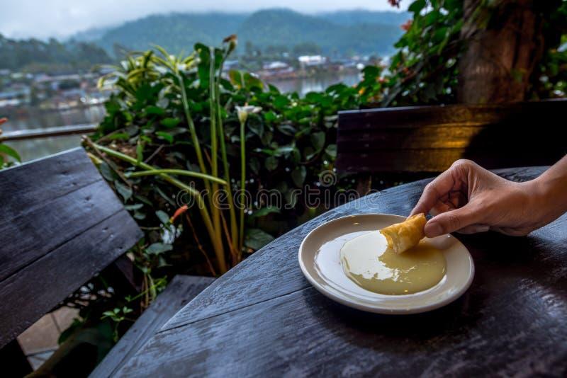 Το τηγανισμένο βρασμένο στον ατμό κουλούρι ήταν εμβύθιση στο γλυκαμένο συμπυκνωμένο γάλα σε ένα κύπελλο με το υπόβαθρο ορεινών χω στοκ εικόνα με δικαίωμα ελεύθερης χρήσης