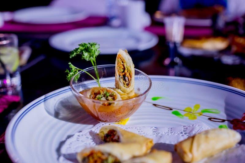 Το τηγανισμένο ελατήριο κυλά με τις κόκκινες και άσπρες σάλτσες, που εξυπηρετούνται στο άσπρο πιάτο με τη φρέσκια πράσινη σαλάτα  στοκ εικόνες