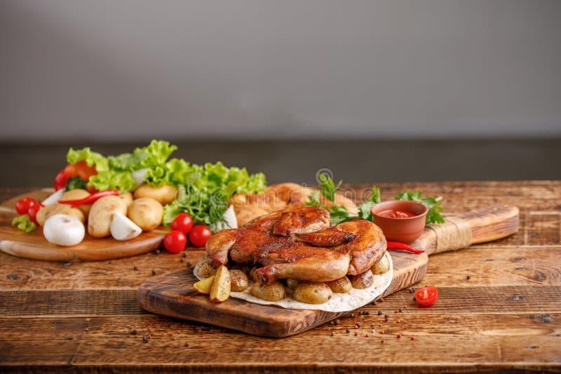 Το τηγανισμένο κοτόπουλο με διακοσμεί των ψημένων νέων πατατών με τα φρέσκα λαχανικά Ορεκτική ακόμα ζωή σε ένα ξύλινο υπόβαθρο στοκ εικόνα με δικαίωμα ελεύθερης χρήσης