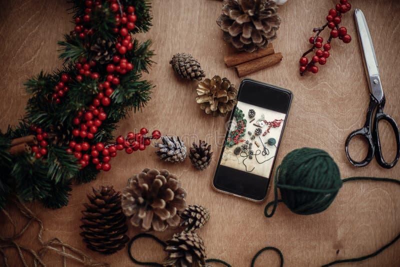 Το τηλέφωνο με τη φωτογραφία του αγροτικού επιπέδου στεφανιών Χριστουγέννων βρέθηκε διαδικασία στοκ φωτογραφία