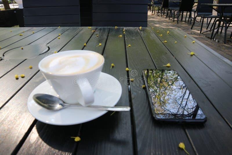 Το τηλέφωνο Smartphone που βρίσκεται στον πίνακα απεικονίζει τα δέντρα στην οθόνη δίπλα σε ένα φλυτζάνι του cappuccino στοκ φωτογραφία με δικαίωμα ελεύθερης χρήσης