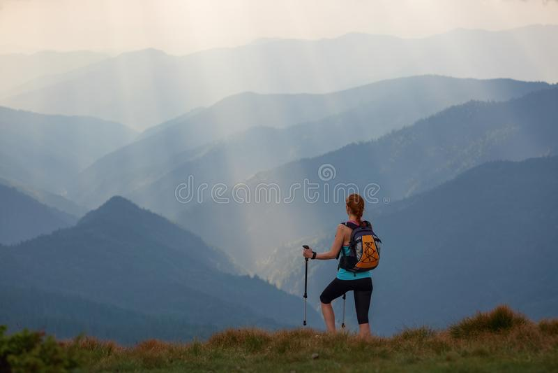Το τοπίο με τα υψηλά βουνά, οι ακτίνες ήλιων έρχεται μέσω των σύννεφων Το ακραίο κορίτσι με τα ακολουθώντας ραβδιά στοκ εικόνες