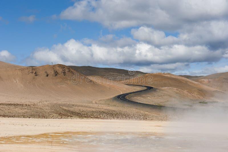 Το τοπίο με το s διαμόρφωσε το δρόμο και τα γεωθερμικά mudpots, Hverir, Namafjall, Ισλανδία στοκ εικόνες