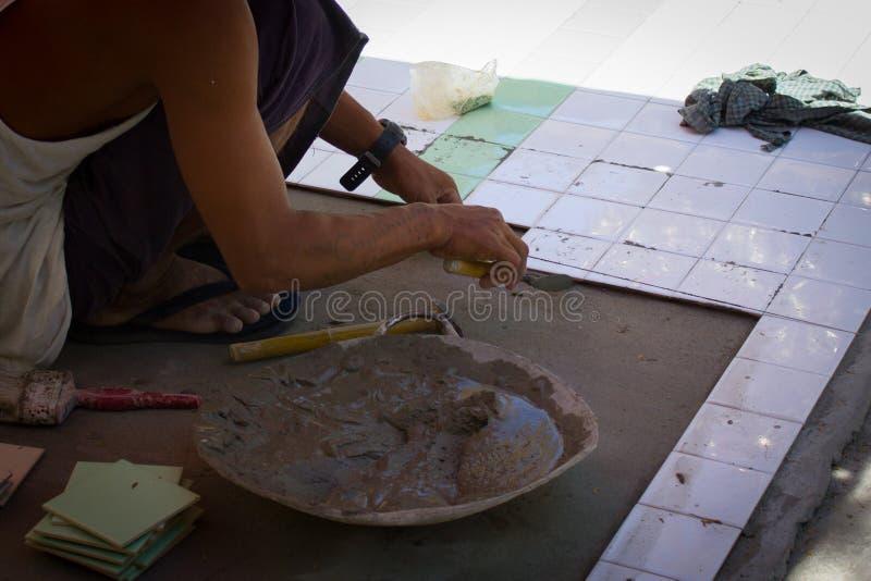 Το τοπικό πρόσωπο εγκαθιστά τα κεραμίδια στο πάτωμα στο ναό στοκ εικόνα με δικαίωμα ελεύθερης χρήσης