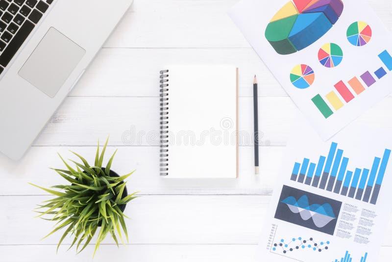 Το τοπ γραφείο γραφείων άποψης με το lap-top, χλευάζει επάνω τα σημειωματάρια και τις εγκαταστάσεις στο άσπρο ξύλινο υπόβαθρο στοκ εικόνες