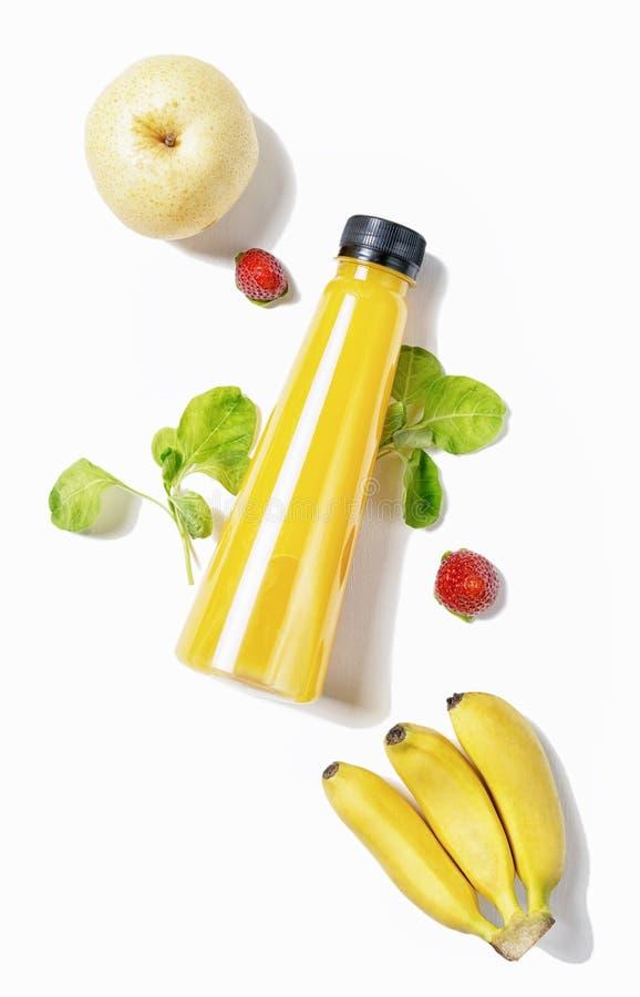 Το τοπ επίπεδο άποψης βάζει το κόκκινο μπουκάλι του χυμού με το σπανάκι, τις φράουλες και το αχλάδι στο άσπρο υπόβαθρο Υγιής τρόπ στοκ εικόνα