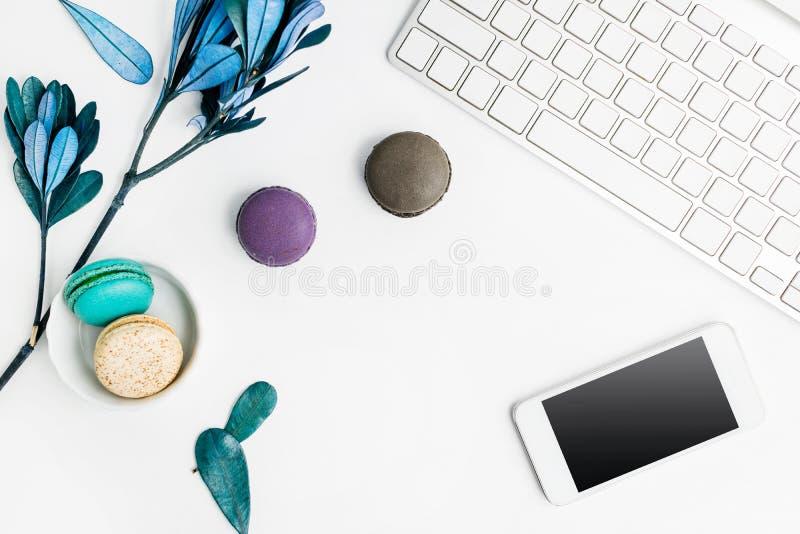 Το τοπ επίπεδο άποψης βάζει τα ζωηρόχρωμα macarons με το πληκτρολόγιο, το τηλέφωνο κυττάρων και τα μπλε φύλλα στον άσπρο πίνακα Δ στοκ εικόνες με δικαίωμα ελεύθερης χρήσης