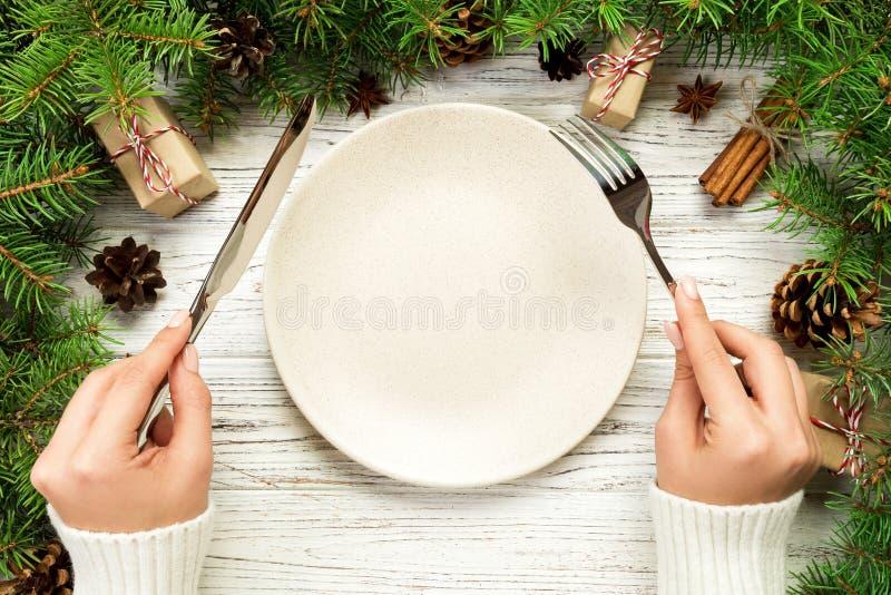 Το τοπ κορίτσι άποψης κρατά το δίκρανο και το μαχαίρι διαθέσιμα και είναι έτοιμο να φάει Κενό πιάτο γύρω από κεραμικό στο ξύλινο  στοκ εικόνα με δικαίωμα ελεύθερης χρήσης