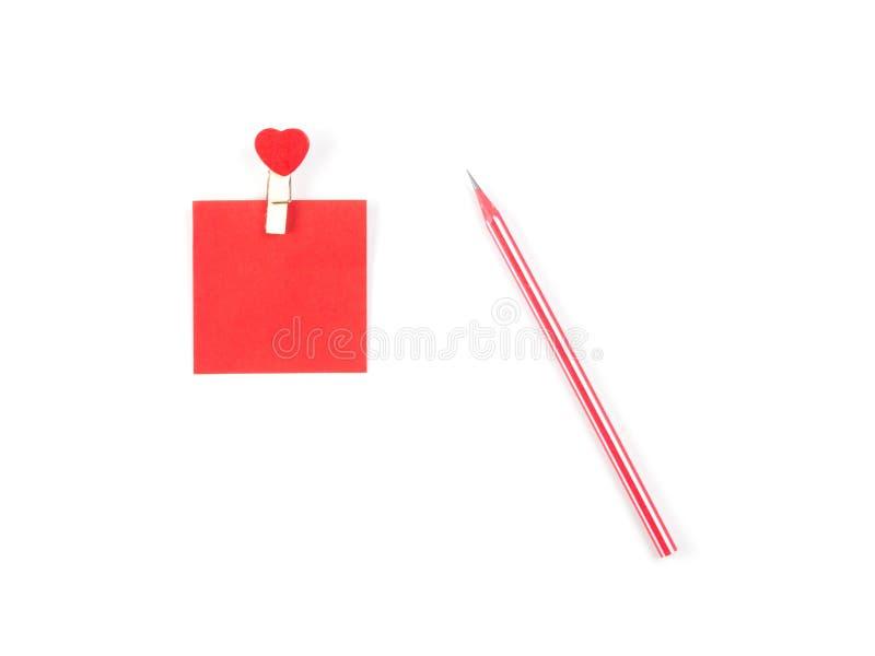 Το τοπ υπόμνημα άποψης κολλά τις κόκκινες σημειώσεις και το κόκκινο μολύβι στο άσπρο backgroun στοκ φωτογραφία