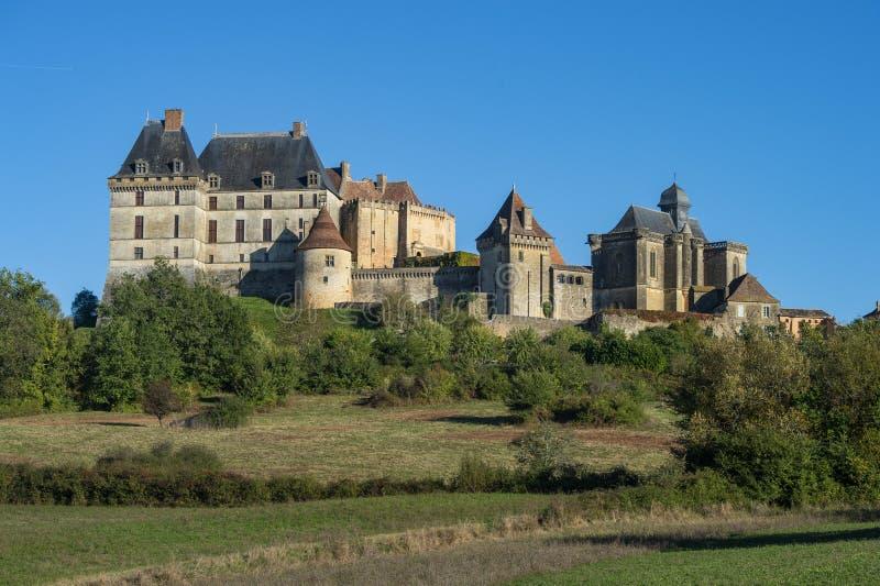 Το τοπ χωριό λόφων και το κάστρο Biron στην περιοχή Dordogne στοκ φωτογραφία