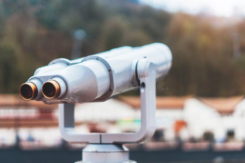 Το τουριστικό τηλεσκόπιο εξετάζει την πόλη με τα βουνά χιονιού άποψης, το μέταλλο κινηματογραφήσεων σε πρώτο πλάνο διοφθαλμικό στ στοκ εικόνα