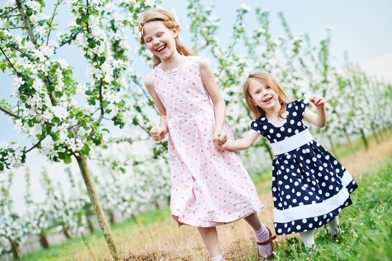 Το τρέξιμο δύο μικρών κοριτσιών και η κατοχή της διασκέδασης καλλιεργούν την άνοιξη στοκ εικόνες