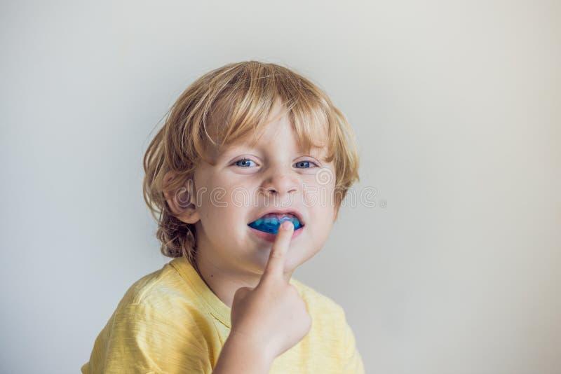 Το τρίχρονο παλαιό αγόρι παρουσιάζει myofunctional εκπαιδευτή για να φωτίσει τη συνήθεια στοματικής αναπνοής Οι βοήθειες εξισώνου στοκ εικόνες