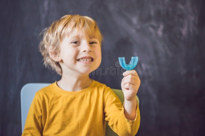 Το τρίχρονο παλαιό αγόρι παρουσιάζει myofunctional εκπαιδευτή Οι βοήθειες εξισώνουν τα δόντια ανάπτυξης και το σωστό δάγκωμα, ανα στοκ φωτογραφίες