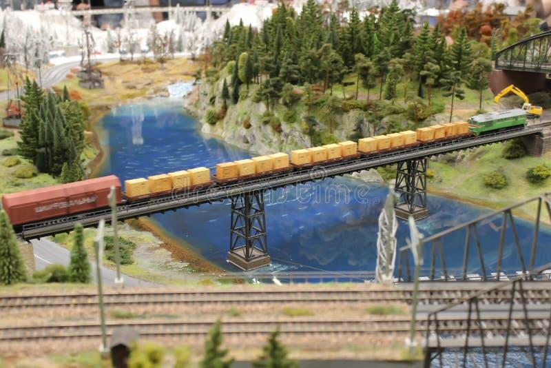 Το τραίνο σιδηροδρόμων οδηγά στη γέφυρα και μεταφέρει τα εμπορεύματα στοκ φωτογραφίες