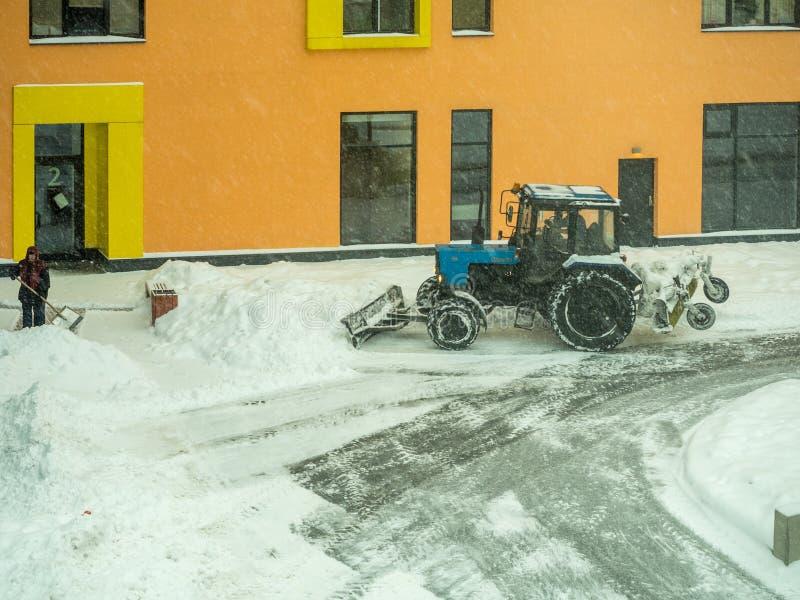Το τρακτέρ καθαρίζει το δρόμο από το χιόνι στοκ φωτογραφία