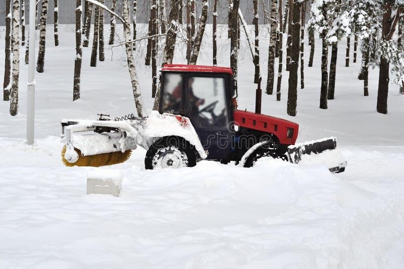 Το τρακτέρ καθαρίζει το χιόνι στο πάρκο στοκ φωτογραφίες